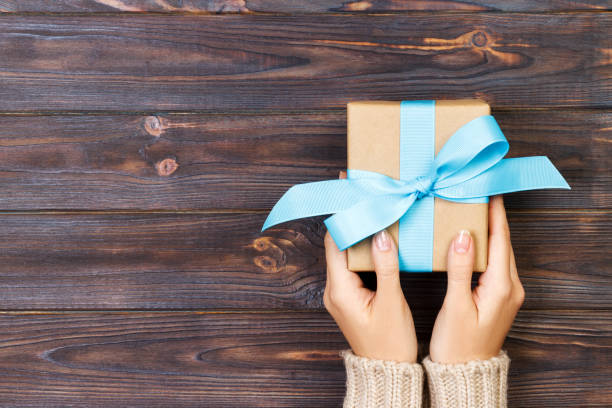 Woman hands give wrapped valentine or other holiday handmade present in paper with red, blue and green ribbon. Present box, decoration of gift on white wooden table, top view with copy space.
